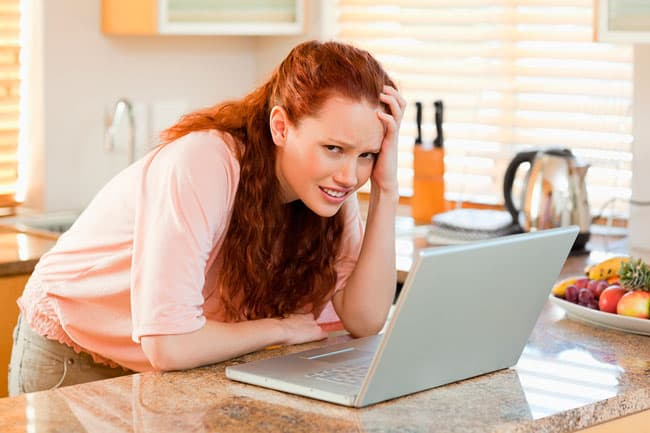 Woman-annoyed-by-her-laptop-in-27565196